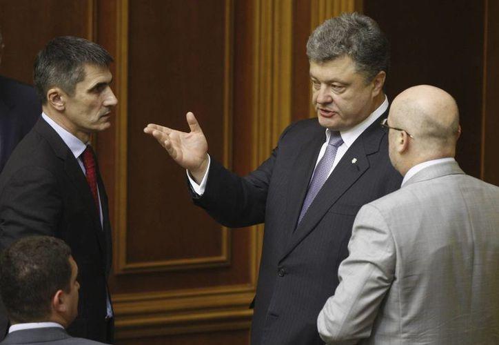 El presidente de Ucrania, Petro Poroshenko (c), conversa con el recién nombrado fiscal general de Ucrania, Vitaly Yarema (i), y el portavoz del Parlamento, Alexander Turchinov (d). (EFE)