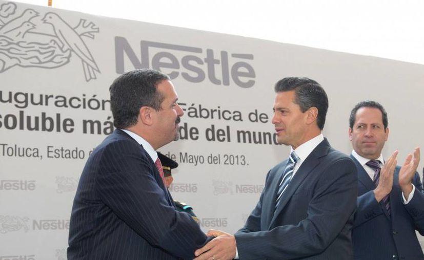 El presidente Peña Nieto saluda a un directivo de Nestlé durante la inauguración de la planta de café soluble más grande del mundo, en Edomex. A la derecha, el gobernador Eruviel Ávila. (presidencia.gob.mx)