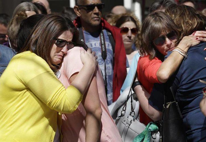 Familiares de las víctimas de la explosión de Boston se abrazan durante un momento de silencio en uno de los dos lugares donde explotaron bombas en la línea de meta del Maratón. (Agencias)