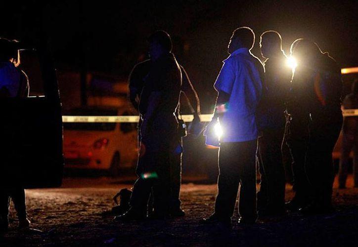 En Chacaltianguis, policías trabajan para el rescate de cuerpos en una fosa clandestina. (excelsior.com.mx)
