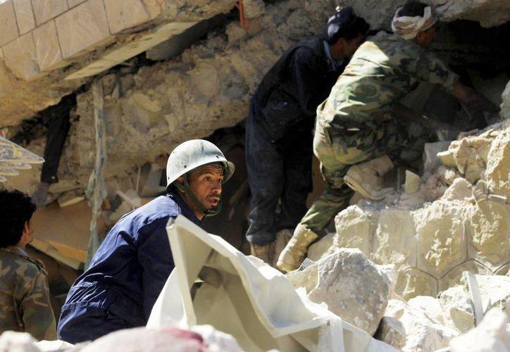 Varios soldados y médicos yemeníes intentan recuperar los cuerpos de los policías muertos entre los restos de la sede principal de la Policía tras un bombardeo de la coalición árabe en Saná, Yemen, hoy 18 de enero 2016. EFE)