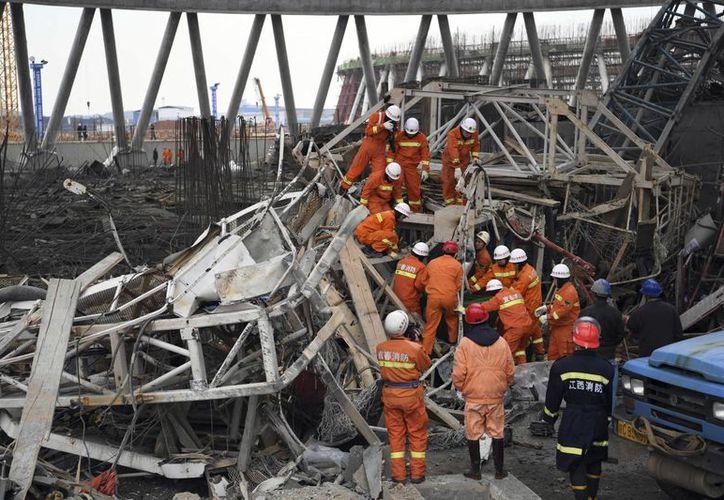 Imagen distribuida por la agencia china de noticias Xinhua, en la que se ven a rescatistas mientras buscan sobrevivientes tras el desplome de una plataforma de trabajo en la planta de generación de energía de la ciudad de Fengcheng. (Wan Xiang/Xinhua vía AP)