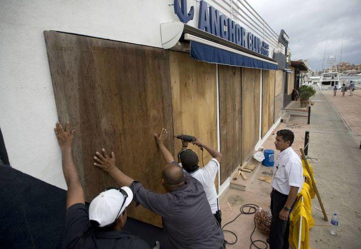 Trabajadores de una tienda cubren las ventanas con madera ante la llegada del huracán Newton. (AP/Eduardo Verdugo)