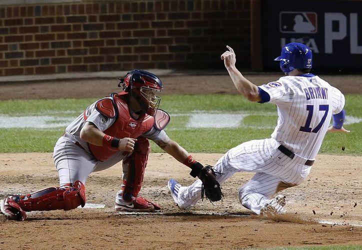 El catcher de Cardenales de San Luis, Tony Cruz (48), poncha a Kris Bryant (17), de Chicago Cubs, que sin embargo ganaron el partido 6x4 para llevarse el campeonato de la Liga Nacional. (AP)