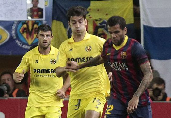 Dani Alves (d) esquiva a Manu Trigueros, jugador del Villarreal, en partido en el que el brasileño se comió un plátano que le arrojó un aficionado racista. (EFE)
