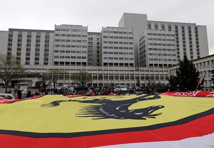 Los signos de mejoría en Michael Schumacher han sido mínimos, y no ha experimentado ninguna respuesta a los estímulos más allá de algunos reflejos puntuales. En la foto, seguidores colocan una bandera gigante frente al hospital de Grenoble, donde el piloto permanece hospitalizado. (Archivo/Efe)