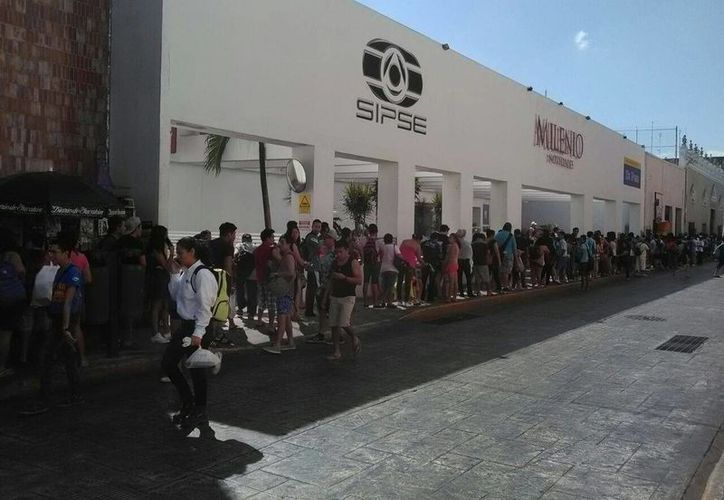 Cientos de personas hacen fila para abordar el autobús a Progreso, para el último día de festejos del Carnaval.(SIPSE.com)
