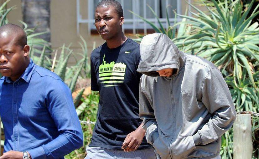 El atleta Pistorius (con capucha y prótesis en ambas piernas) fue detenido la mañana de este jueves. (Agencias)