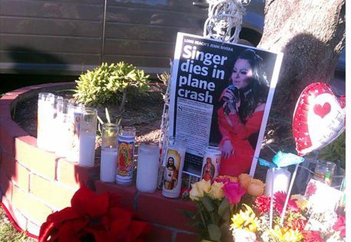 Varios seguidores de Jenni Rivera armaron un altar en honor de la cantante afuera de la casa de sus padres en el que le han dejado flores, mensajes y veladoras. (Agencia Reforma)