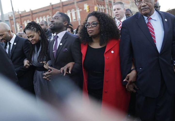 La conductora de televisión Oprah Winfrey participa en una marcha junto con David Oyelowo (izquierda, quien interpretó a Martin Luther King Jr. en la película Selma), Ava DuVernay (izquierda, directora de Selma) y el rapero Common (a la extrema izquierda), hacia el puente Edmund Pettus en honor de Martin Luther King Jr. en Alabama. (Agencias)