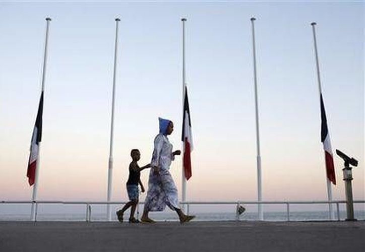 Una mujer y su hijo pasan por delante de banderas francesas a media asta cerca del lugar donde se produjo un letal atentado, en Niza, Francia. (AP)