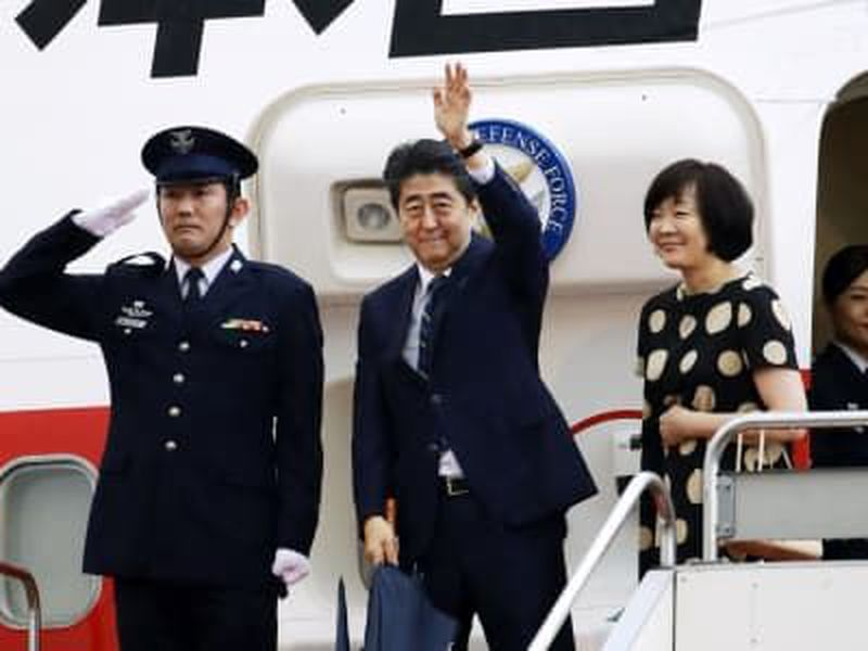 Japanese Prime Minister Shinzo Abe, center, and his wife Akie prepare to leave for the U.S. at Haneda international airport in Tokyo.