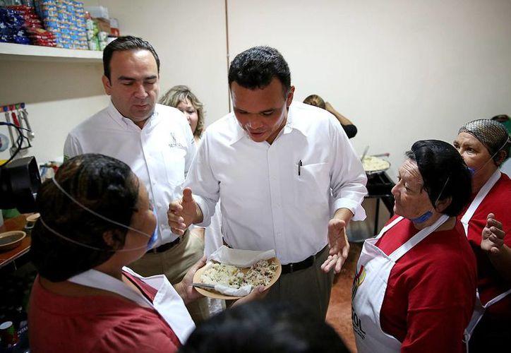 El gobernador de Yucatán, Rolando Zapata Bello, recibe un plato de comida en el nuevo Comedor del bienestar en la colonia Nueva Reforma Agraria. (SIPSE)