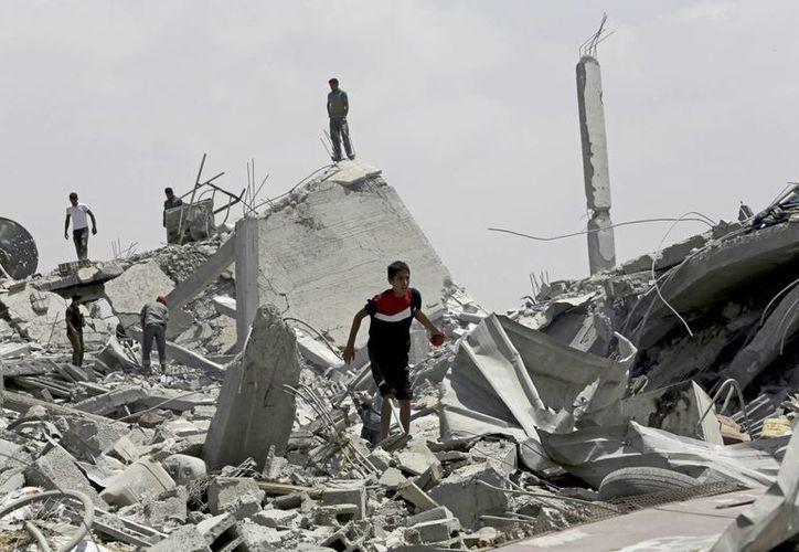 Palestinos buscan algunas cosas que puedan rescatar entre los escombros de sus viviendas destruidas por bombardeos de Israel, en Khuzaa, este de Khan Younis, en el norte de la Franja de Gaza. (Foto:AP)