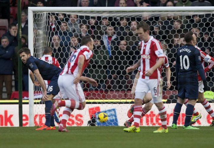 Michael Carrick (i) reacciona con tristeza al darse cuenta del autogol cometido frente al Stoke. (Agencias)