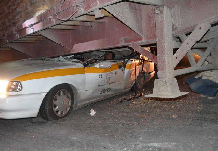 Un taxi quedó incrustado bajo un tráiler de cemento. (Redacción/SIPSE)