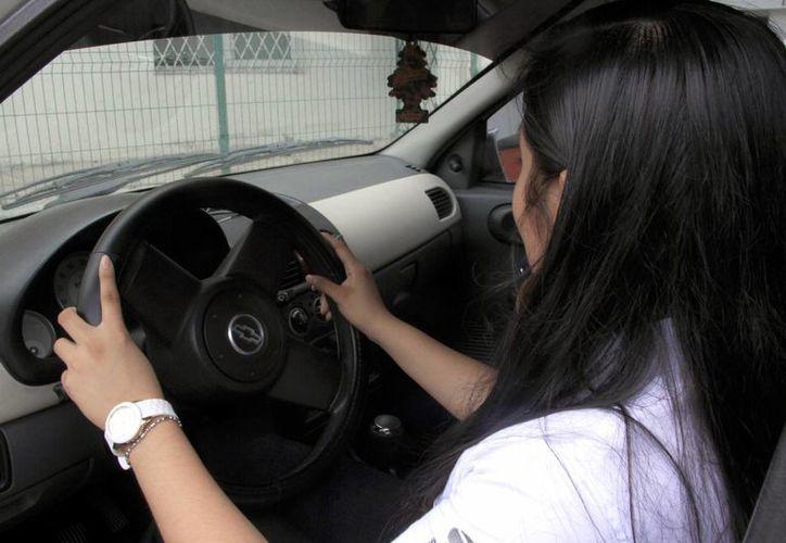 Las escuelas de manejo son una buena herramienta para los ciudadanos, ya que cambian la mentalidad de una persona al comenzar a conducir un vehículo. Imagen de una mujer al volante. (Archivo/SIPSE)