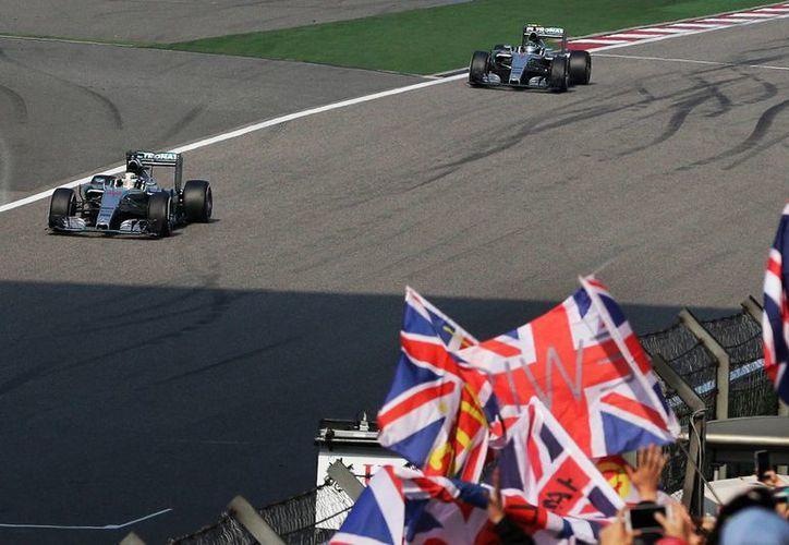 El inglés Lewis Hamilton, de la escudería Mercedes, avanza por delante de su coequipero Nico Rosberg al término del Gran Premio de China. (Foto: AP)