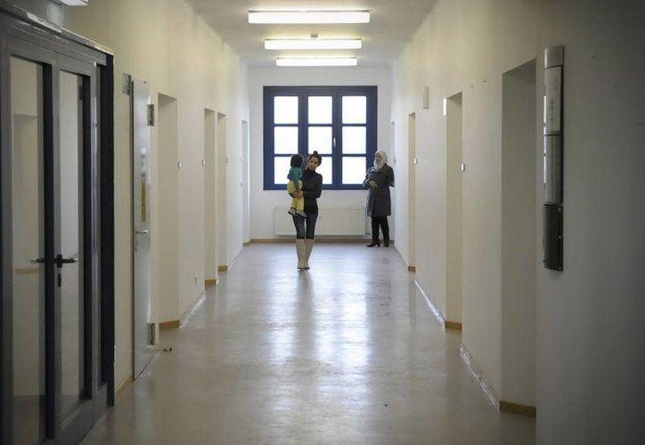 Refugiados sirios caminan por el pasillo del albergue Oderland en Fráncfort, Alemania. (EFE)
