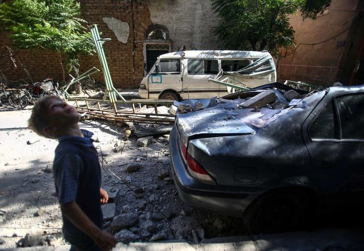 Un niño camina junto a vehículos y edificaciones dañados por un ataque aéreo en Douma, Siria. (Archivo/EFE)