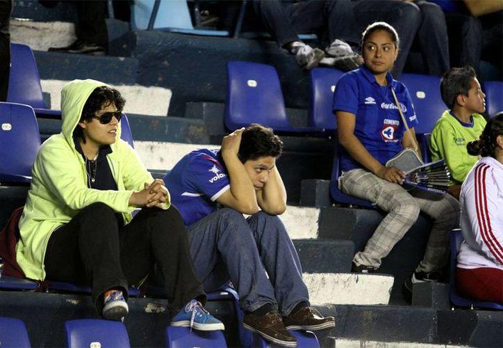 Cruz Azul empató ayer a un gol con Toluca, en el partido de vuelta de la Liguilla de la Liga MX. En la imagen, aficionados azules lamentan la eliminación, al final del encuentro en el estado Azul. (NTX)