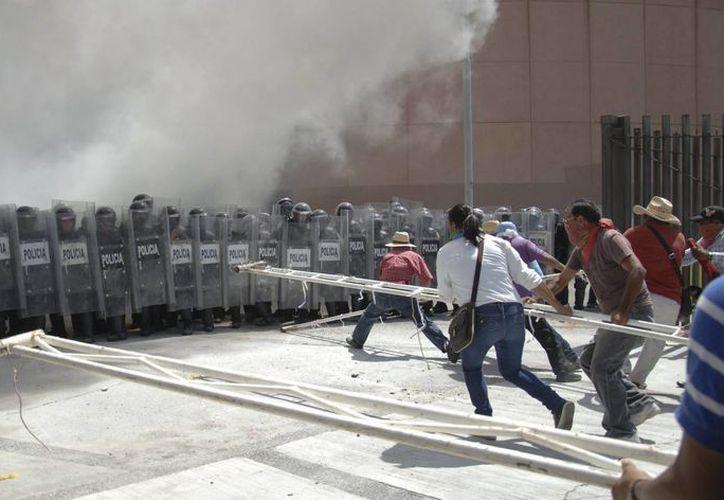 Cientos de alumnos de la Normal de Ayotzinapa intentaron irrumpir en el Congreso de Guerrero, pero fueron contenidos por la policía. (AP)