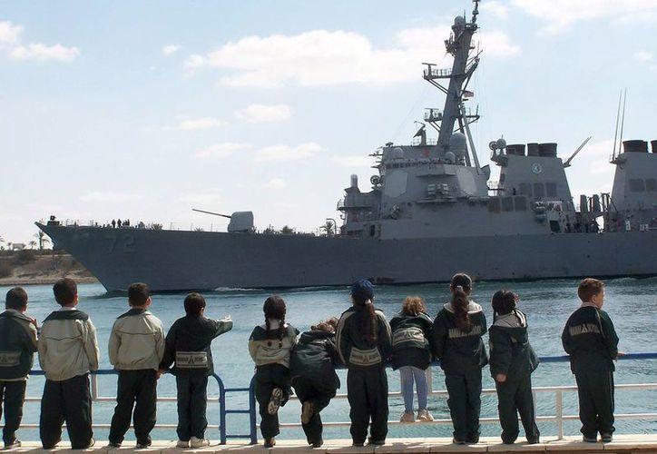 Varios niños observan el destructor estadounidense USS Mahan mientras cruzaba el Canal de Suez (Egipto) en 2009, En ese vehículo se produjo un tiroteo este lunes por la noche. (EFE/Archivo)