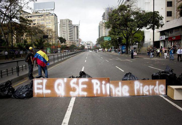 """Manifestantes venezolanos se reúnen junto a una barricada con un cartel que dice : """"El que se rinde pierde"""" en Caracas, Venezuela. (Agencias)"""