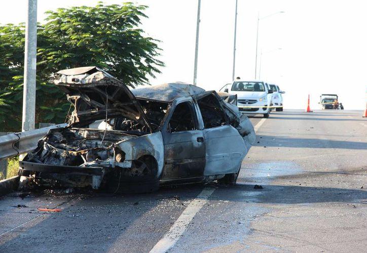Un vehículo que chocó contra el muro de contención del puente Xcanatún, en la Mérida-Progreso, se incendió. El conductor murió quemado. (Aldo Pallota/SIPSE)