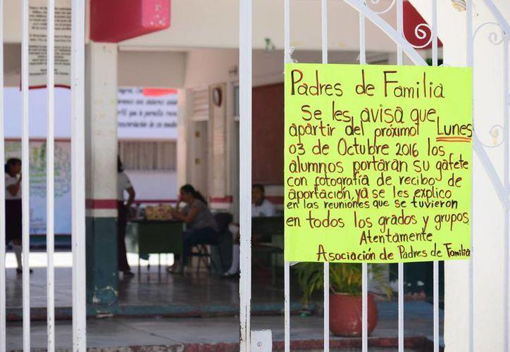 Con un letrero a la entrada del plantel se advierte a los padres de familia de la resolución tomada. (Gustavo Villegas/ SIPSE)