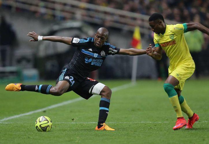 El defensor francés de Marsella, Rod Fanni (i), disputa el balón al delantero de Nantes, Serge Gakpe, en partido ganado por los segundos. De esta forma Marsella pierde por tercera vez en fila y ya no podrá ganar la liga de Francia. (Foto: AP)