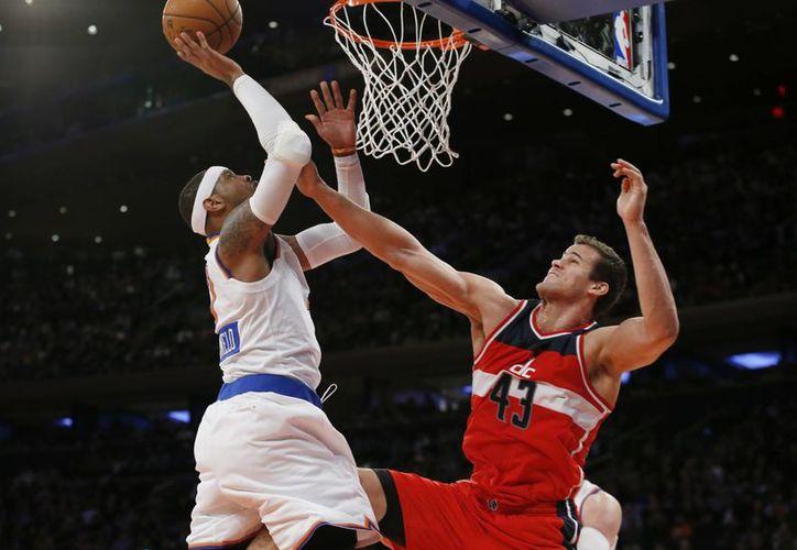 Carmelo Anthony (7) sacó la cara nuevamente por Knicks. En esta gráfica lanza la pelota por sobre Kris Humphries (43), de Wizards. (Foto: AP)