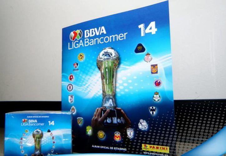 En la portada, el álbum Panini del torneo Apertura 2014 de la Liga MX ostenta el trofeo del campeonato y los escudos de los 18 equipos de la Primera División. (Facebook/Liga Bancomer MX)