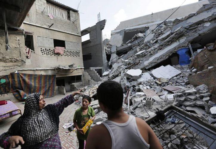 La palestina Heygar Jendiyah, izquierda, señala el lugar donde se encontraba su casa, destruida por un ataque aéreo israelí, acompañada por sus hijos Ranin, centro, y Helmi, en el barrio Sabra de Ciudad Gaza. (Agencias)