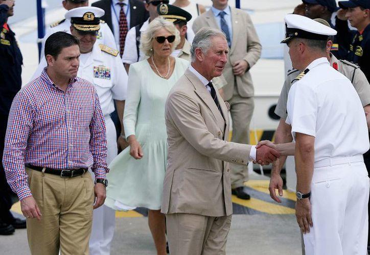 El príncipe Carlos de Inglaterra y su esposa Camila, duquesa de Cornualles (c), acompañados del ministro colombiano de Defensa, Juan Carlos Pinzón (d), visitaron la estación de guardacostas de la Armada de Colombia, en Cartagena. (EFE)