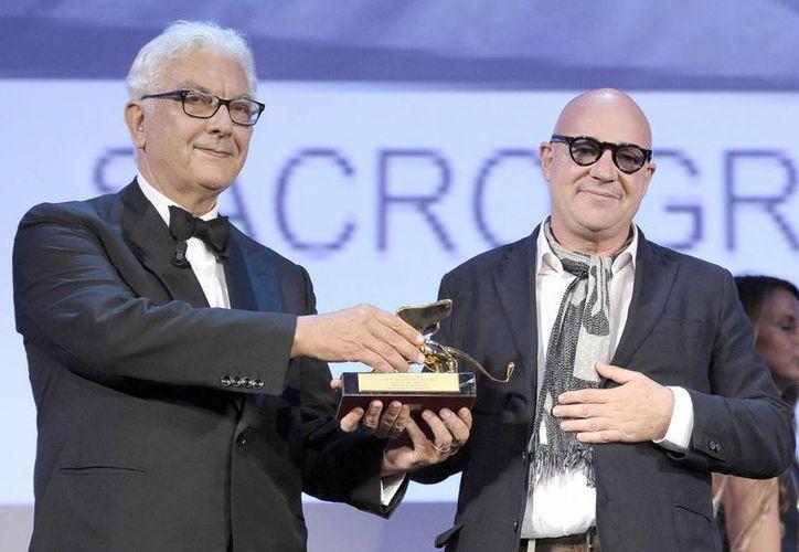El cineasta Gianfranco Rosi (d) recibe el León de Oro del presidente de la 70 edición del Festival de Venecia, Paolo Baratta. (EFE)