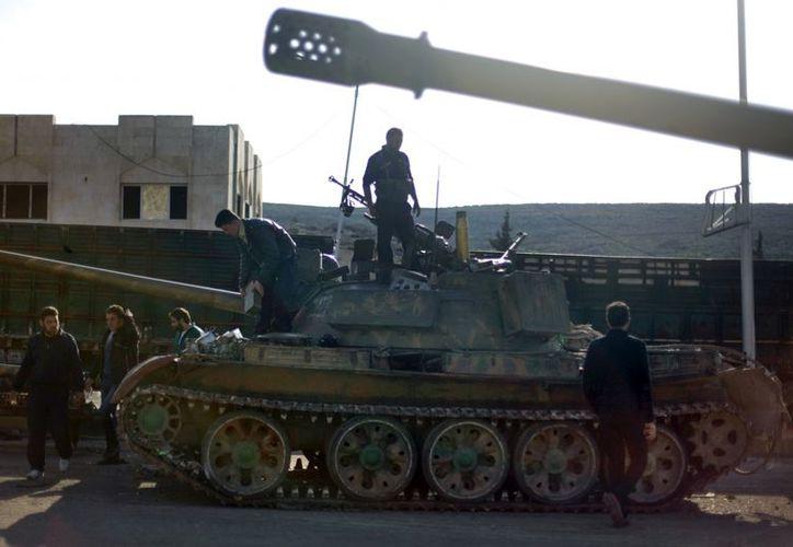 Rebeldes sirios revisan el estado de un tanques después de tomar una base militar en Alepo. (Agencias)