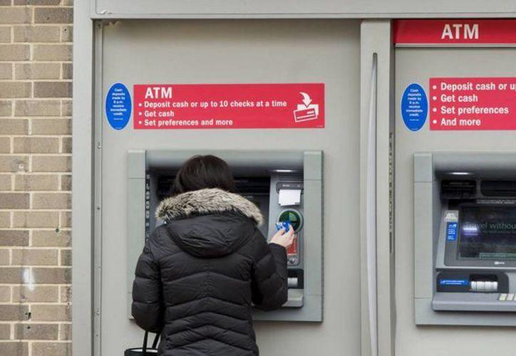 Una cliente retirando dinero de un cajero automático (Saul Loeb/AFP)