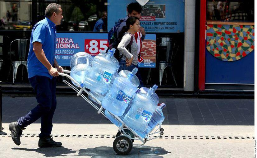 Actualmente las familias jaliscienses invierten en promedio $30 por un garrafón con agua; sin embargo, de concretarse la iniciativa generaría un ahorro al ser gratuito. (Agencia Reforma)
