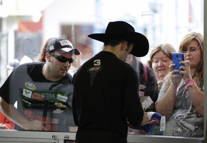 Austin Dillon se toma un momento durante una pausa por lluvia para firmar autógrafos. (Foto: Agencias)