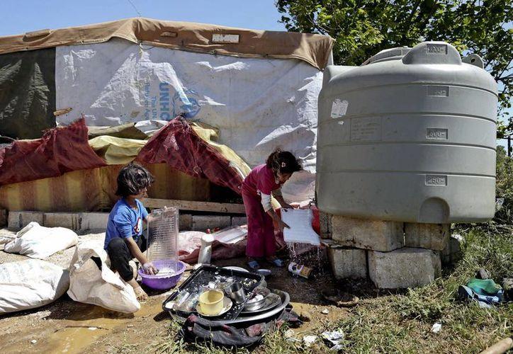 Niñas sirias lavando utencilios afuera de su tienda de campaña en un campo de refugiados sirios cerca del poblado de Kab Elias, Líbano. (Agencias)
