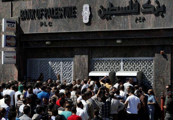 Imagen de palestinos reunidos ayer para sacar dinero de cajeros automáticos en Ciudad de Gaza. (Agencias)