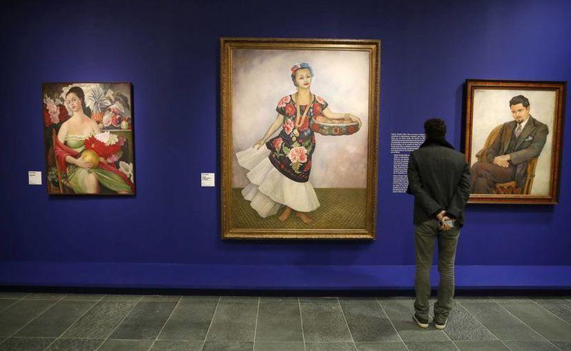 """Un visitante contempla la obra 'Retrato de Dolores Olmedo (c), de Frida Kahlo, que se expone en la muestra """"Frida Kahlo - Diego Rivera. Arte en Fusión"""" en el museo Orangerie, en París. (EFE)"""