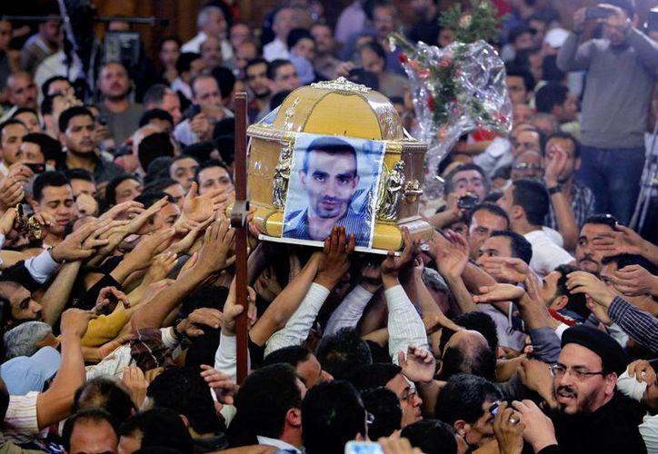 Cristianos coptos en el funeral de cuatro de ellos, y un musulmán, que murieron el sábado en una aldea al norte de El Cairo. (Agencias)