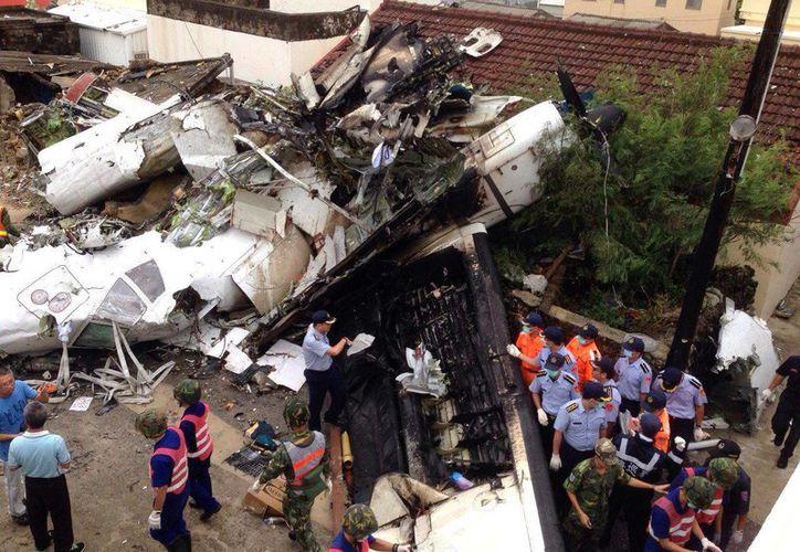 Policías y soldados vigilan en el lugar donde un avión de la compañía TransAsia Airways se estrelló al realizar un aterrizaje de emergencia en medio de un fuerte temporal en las islas Penghu (Pescadores), en Taiwán. (EFE)