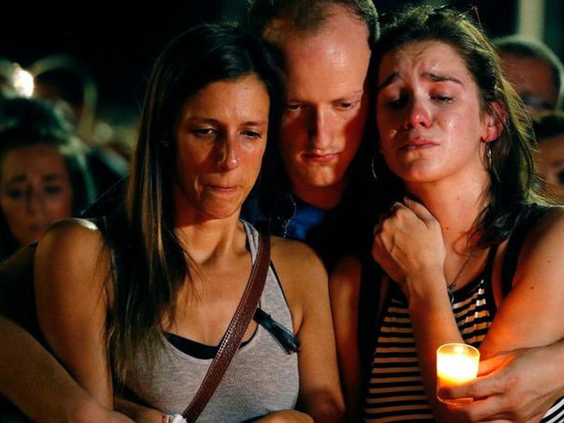Mallory Cunningham, left, Santino Tomasetti, center, and Aubrey Reece attend a candlelight vigil.