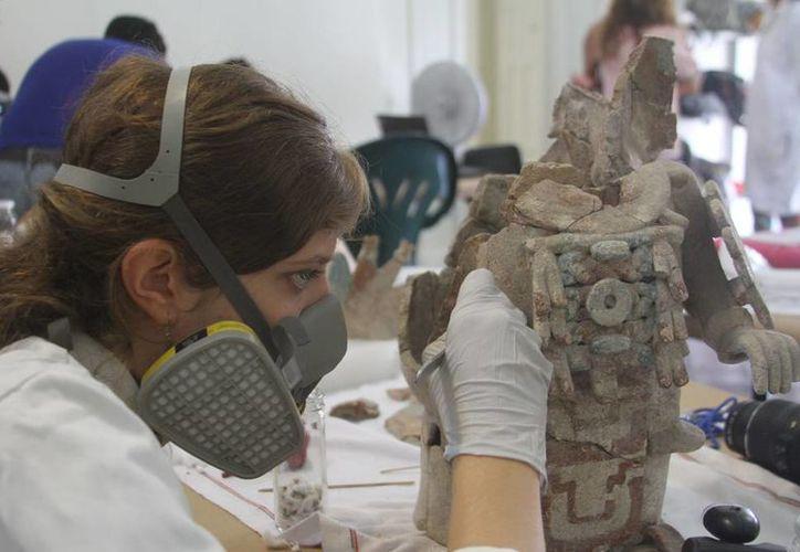 Una de las alumnas de la Escuela de Restauración y Museografía de la Ciudad de México en el proceso de limpieza y fijado de una de las piezas del Palacio Cantón de la ciudad de Mérida, Yucatán. (César González/SIPSE)