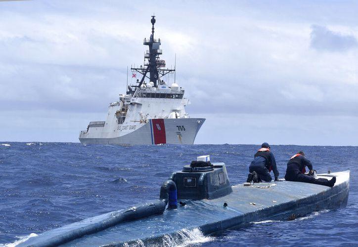 Esta foto del 19 de junio del 2019 proporcionada por los Guardacostas de EE.UU. muestra a efectivos del barco Munro, de los Guardacostas de EE.UU, inspeccionando un semisubmarino en aguas internacionales en el oriente del océano Pacífico. (Guardacostas de EE.UU. via AP)