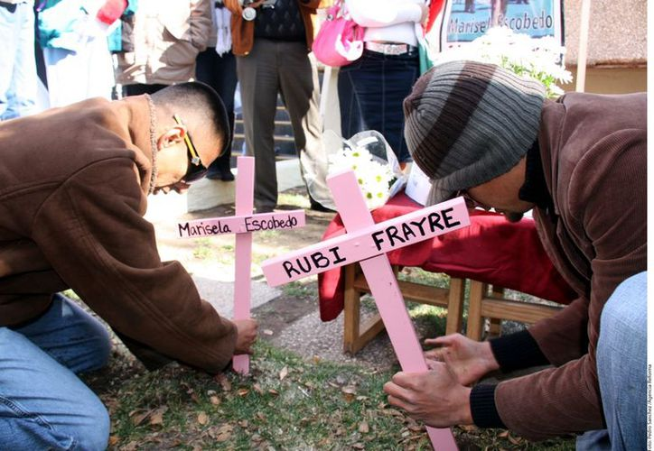 Familiares de Marisela Escobedo y Rubí Marisol Frayre colocan cruces para honrar su memoria. (Reforma)