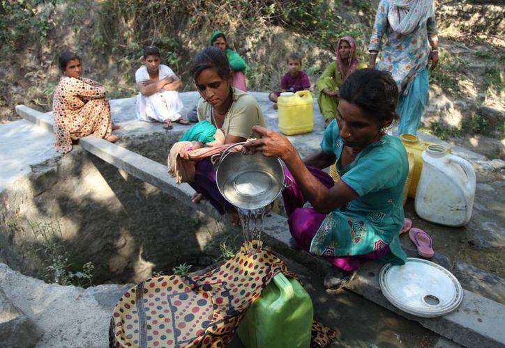 Mujeres recolectan agua para beber ante la fuerte ola de calor que afecta a la India. (AP)